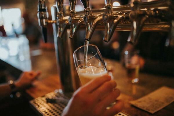 Bild på person som håller i ett ölglas och häller upp öl i en bar